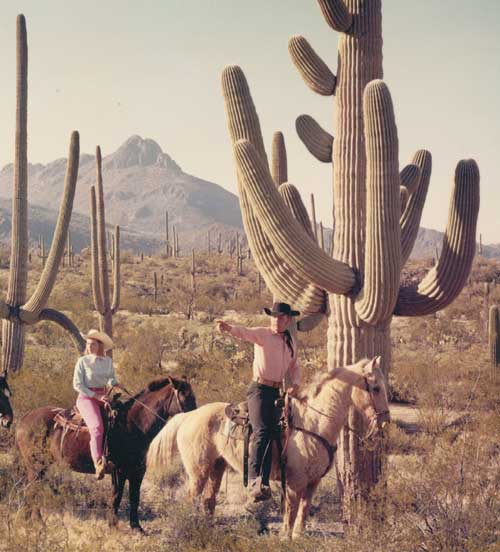 image: Don and Barbara on horseback in the desert.